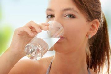 Cô gái đang uống nước, lợi ích của nước ấm
