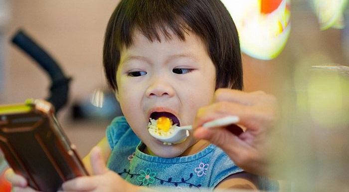 Trẻ được dụ ăn bằng cách cho xem điện thoại thông minh